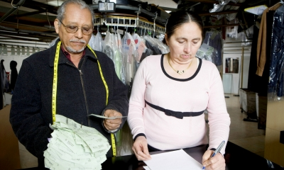 Man and a woman stood at the front of a family dry-cleaning business