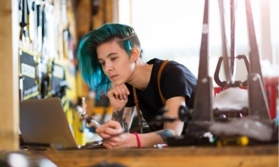 Female worker with blue hair looking for music on her laptop