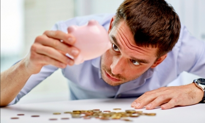 Man in a blue shirt looking into an empty piggy-bank with coins on the table