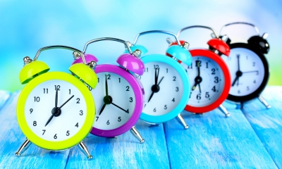 Row of multi-coloured alarm clocks