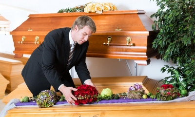 Man laying flowers in a brown coffin