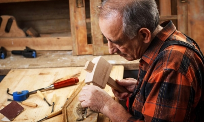 Old man using hammer and chisel on wooden furniture