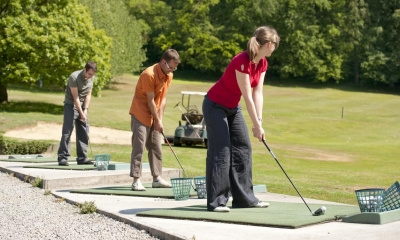 Multiple people playing golf at a driving range on a sunny day