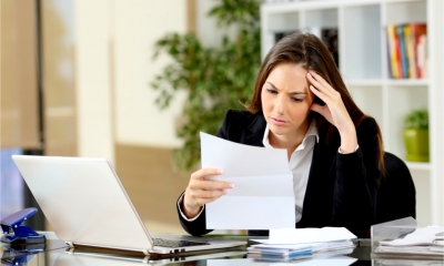 Businesswoman reading letter looking troubled