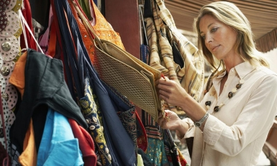 Woman looking through variety of bags in outdoor market