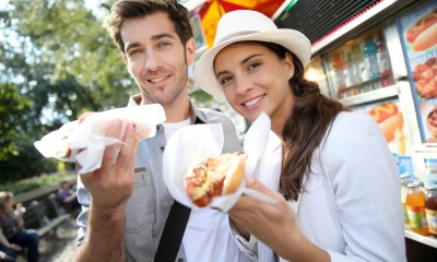 Man and woman eating hot dogs outside hotdog stand