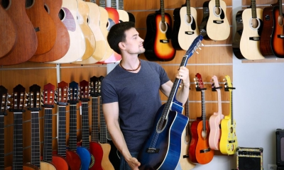 Man holding blue guitar with multiple guitars in background in music shop