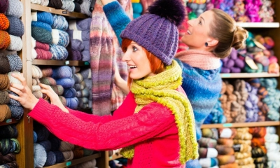 Woman in hat looking through various bundles of wool on shelf with woman in background