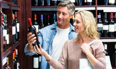 Man and woman holding bottle of red wine in an off-licence with wine in background