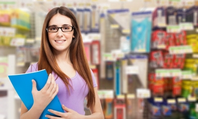Woman in glasses holding blue document with office supplies in background