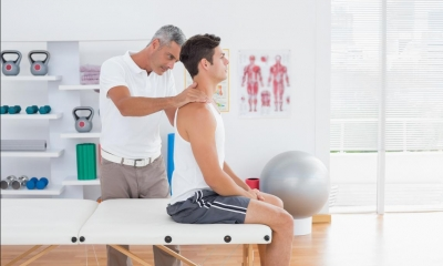 Customer sitting on bench receiving back massage from osteopath