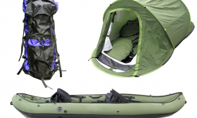 Large backpack, tent, and blow up canoe with white background