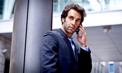 Man in a suit looking past the camera while on the phone