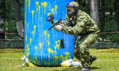 Person playing paintball holding gun in with blue bag in background