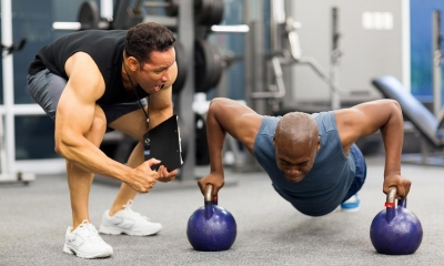 Personal trainer motivating client who is using barbells to do pushups