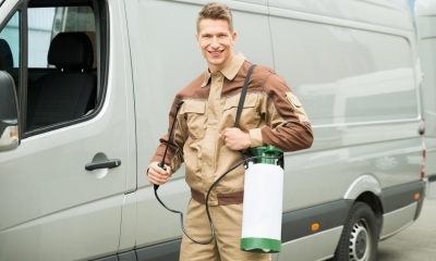 Man in brown work clothes holding pest control machine in front of silver van
