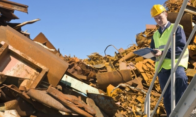 Man in high visibility vest in metal scrapyard with blue skies in background