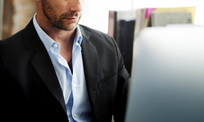 Cut-off picture of business man looking at laptop