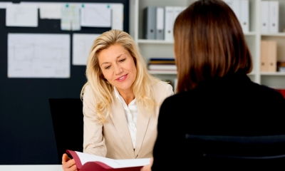 A female HR manager meets with a female employee to discuss her employment