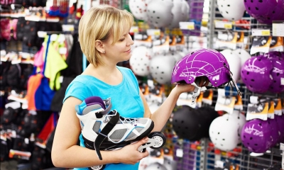 Woman holding roller blade and purple helmet in sports shop