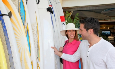 Man showing customer multiple different surfboards in surf shop