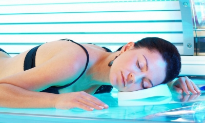 Woman in black bikini lying face down in sunbed