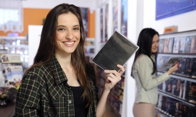 Woman holding DVD  in rental shop with woman in background looking for DVD