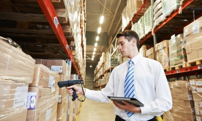 Man in warehouse scanning packaged products on shelf
