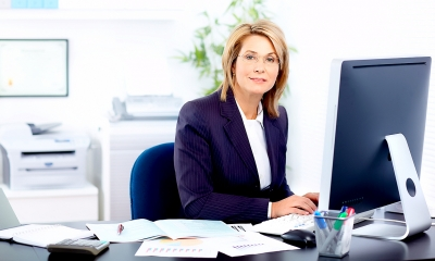 Business woman sitting at a desk typing on her computer keyboard