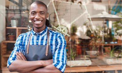 Portrait of a handsome young African entrepreneur smiling and standing with his arms crossed in front of his trendy cafe