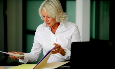Older woman in a white shirt filing her company's confirmation statement