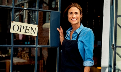 Happy woman owner showing open sign in her small business shop.