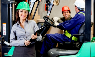A female supervisor and delivery drivers in a warehouse wearing the correct safety gear.