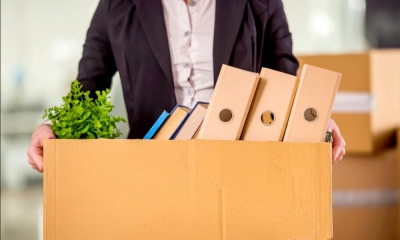 Employee leaving office with box containing plant and files