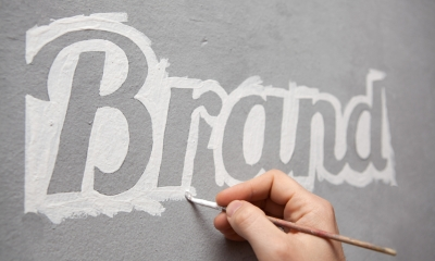 The word Brand is outlined in white paint on a grey background