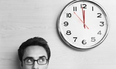Male employee looking at clock on wall