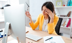 Businesswoman having head pain in office wring a bright orange jacket