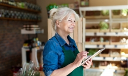 Old entrepreneur assistant with digital tablet in small grocery store