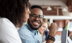 Close up of smiling African American employee look at female colleague chatting in office