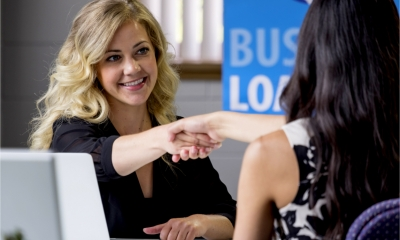 A female loans specialist shakes hands with a small business owner applying for bridging finance.