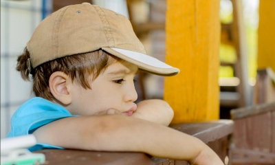 Little boy wearing a cap resting on a wooden fence