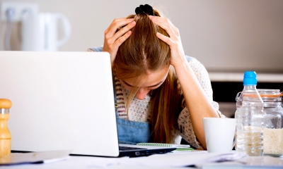 Woman holding her head in her hands next to a laptop after claiming constructive dismissal