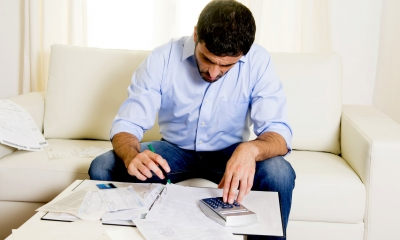 Man in a blue shirt sat on a sofa using a calculator to work out the cost of a divorce