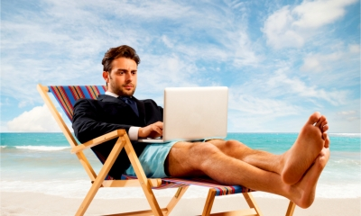 A business man reads the news on his laptop whilst sat in shorts in a deckchair
