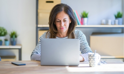 Middle age senior woman sitting at the table at home working using computer laptop Relaxed with serious expression on face