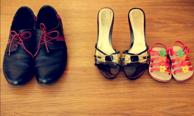 Pair of male shoes lined up next to a pair of female shoes and a child's shoes