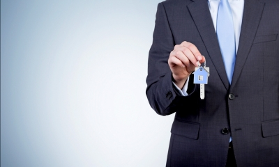 Man in suit holding a set of keys to a property