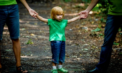 Little child holding both parents hands on dirt trail