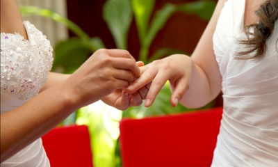 One woman placing the ring on another woman's finger to unite their civil partnership