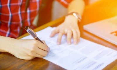 Person in a red shirt writing on a divorce form using a black pen